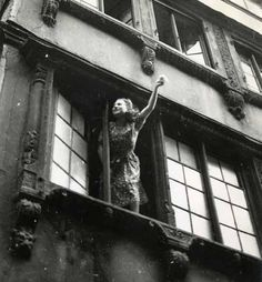 Robert Doisneau. Woman at the Window, circa 1945.  You could make up a story for this one......end of war and she is thanking the troops who came to set them free of Hitler.