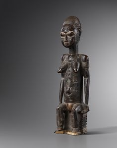 A rare seated Baule figure of 40 cm. The Baule carvers from Central Ivory Coast are known for their detailed rendering of the human body. The anatomic details such as hair, fingers and toes, muscles and scarification marks are carved with extreme delicateness.