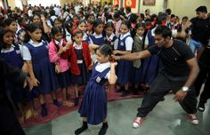 An Indian instructor (2R) shows a self defence technique to a school girl during a self-defence classes at a school in Mumbai on January 4, 2013. After nearly three weeks of lurid reporting on a horrifying gang-rape in New Delhi, women in the Indian capital say they are more anxious than ever, leading to a surge in interest in self-defence classes. AFP PHOTO/ PUNIT PARANJPE