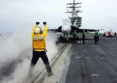 """Aviation Boatswain's Mate (Handling) 3rd Class Gary Armstrong, from Chicago, directs an F/A-18F Super Hornet assigned to the """"Flying Eagles"""" of Strike Fighter Squadron 122 on the flight deck of the aircraft carrier USS Ronald Reagan (CVN 76).  (U.S. Navy photo by Mass Communication Specialist 3rd Class Charles D. Gaddis IV/Released)"""