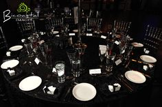 wedding reception table setting and decor. nice black and white contrast. focus is away from the centerpiece and on the dishes. & Black tablecloths with white candle wedding centerpiece decor photo ...