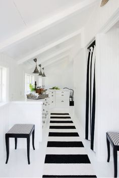 Beach house in black and white Simple kitchen where the white doors almost merges with the white painted floor. To create a contrast to all the white Pernille added some stripes in the form of carpets and curtains.