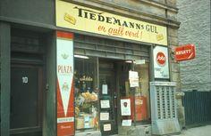 Gatebilde. Butikklokale med reklame for tobakk. Tiedemanns gul og Plaza sigaretter