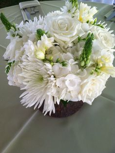 Green and white floral centerpiece in bark covered container.  Rustic centerpiece containing white Spider Mums, Freesia, Hydrangea, Roses, and Star of Bethlehem.