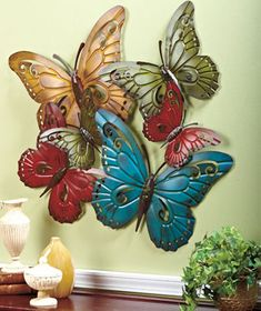 Oversized metal butterfly wall sculpture, painted in a vibrant color palette. It mimics the movement of butterflies in flight! I love butterflies and vivid colors! <3