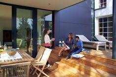 Anbau an Einfamilienhaus: die überdachte Aussenterrasse mit großen Holzstufen