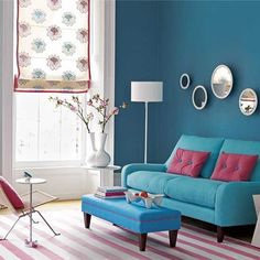 Shades of blue and raspberry living room with striped rug and Roman shade