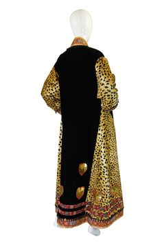 Caftan-style coat (back view) | Franco Moschino (Italian, 1950-1994) | Italy, 1980's | The cut is loose and almost Middle Eastern in feel. Made from a fine, soft, cotton velvet mixed with a faux leopard print that is a startling and bold combination. All the edges are done in thick panels of brocade and this is lined with a panel of bead work with various sized beads. More brocade and braided ribbon is set near the hem. Gold sequin hearts - each edged in a red yarn, hand stiched into place