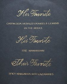 The hand-lettered bar menu spelling out the specifics of their signature cocktails—one his, one hers, and one theirs.