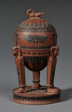 Wedgwood Rosso Antico Egyptian Vase and Cover, England, early 19th century, chocolate-brown ground with crocodile finial, applied black basalt hieroglyphs in relief to a bowl supported by three sphinx-topped legs set on a raised circular base, impressed mark, ht. 8 in.