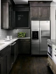 dark black brown cabinets & stainless steel appliances w/ subway tile tiles, also notice the setup w/ microwave in the island, sink at window, fridge out of the way, great kitchen