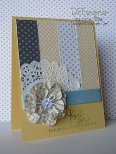 A card with a paper flower and a doily