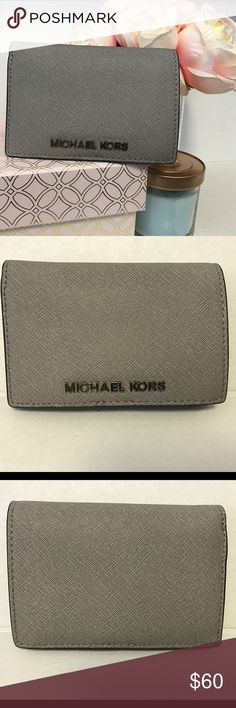 AUTHENTIC Michael Kors Jet Set Wallet (Medium) Gray, Saffiano Leather with Silver Hardware. 6 credit card slots, 2 slots for cash, coin zipper pouch, and clear ID window. Slim design with snap closure. Like brand new! No scratches, stains or tears. No Trades, Poshmark Only. Michael Kors Bags Wallets