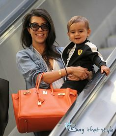 Kourtney Kardashian's love her sense of style! Gold Bangles - Cartier. Love the cat-eye sunglasses and cute bag. Best accessory?  Mason!!
