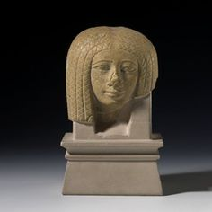 Front of the head from a yellow limestone female figure shown wearing a heavy wig.