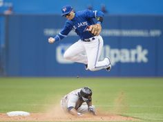 Toronto Blue Jays' Troy Tulowitzki, top, leaps over <-- not going to lie, I believe Tulo is one of the smartest players on baseball. He's always seeming to be a step ahead and can read the strike zone like nobody's business! Braves Baseball, Baseball Players, Softball, Blue Jay Way, Go Blue, Baseball Toronto, Troy Tulowitzki, Hockey, America's Pastime