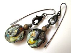 Two crubbly lampwork glass paddles from NuminosityBeads have been stacked with grungy metal bead caps and vintage wood beads. They dangle simply from