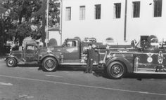 Orange Fire Department fire trucks, Orange, California, ca. 1950. Image shows unidentified fireman standing next to three fire trucks parked on the south side of the Orange Fire Station, located at 153 South Olive Street. Fire trucks left to right are a 1936 International salvage squad, a 195 and 195C Seagraves/FMC pumper. opl2249