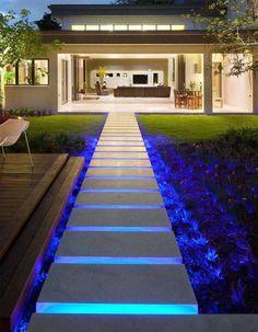 éclairage extérieur LED bleu, allée en pierre naturelle et jardin moderne d'une maison design