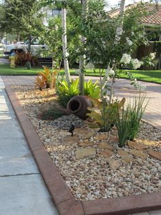 Great idea for low water - low work gardening/landscaping for the hell strip in front of a driveway or sidewalk. Pavers, gravel, rocks, succulents. Pavers & trim for rock garden tropical landscape