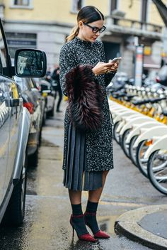 Long sweater with a pleated skirt and dark grey socks with cranberry heels.