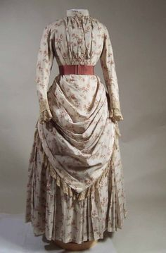Dress, 1887-1888.  Cream tabby weave wool printed with sprays of berries in pink, green and blue. Two piece.    Lined with white cotton satin. Centre front fastening with buttons. Narrow standing collar. Watch pocket attached to left front at bust level. Hem boned with white tape. Sleeves with turn-back cuff stitched to falling cuff, both lace. Separate skirt, fastening centre back. Draped overskirt edged with lace. Pleated band at waist with pleated bow centre front. Underskirt with channels...