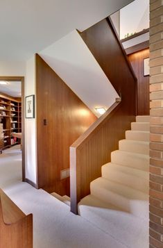Another view of the staircase with walnut walls and brick