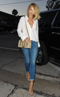 Rosie Huntington-Whiteley is casual, yet fashion-forward, in cuffed jeans, nude sandals, and a loose white button-up blouse.