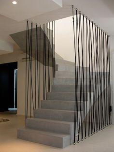 Les tiges métalliques entourent l'escalier bétonné pour une impression de grandeur