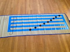 $3 Note Lesson Mat made from Dollar Tree items (mat, tape, board pieces from checkers game). Student can either toss the pieces (notes) onto the staff and identify the note names or place pieces on staff to create 'words' made from the music alphabet.