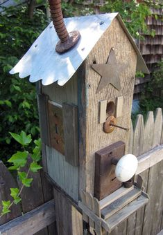 Birdhouse with old door knobs, light cover swtich plate, odds and ends of metal cut outs, rusty spigot, faded wood, adorable!