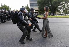 """The young woman's stoic pose drew comparisons to Rosa Parks's refusing to give up a seat at the front of a segregated bus or """"tank man"""" facing down war machines in Tiananmen Square.  Some likened her to a modern-day Statue of Liberty, guiding a bitterly divided country back toward the proper path.  Others called her a """"superhero."""""""