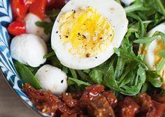 Auch perfekt als Grill-Beilage geeignet: Rezept für Rucolasalat mit Antipasti, Mozzarella und Ei.