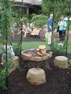 Saw this at Epcot... love the tree stump as a table and logs wrapped in burlap for seating!