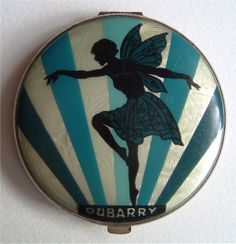 Dubarry art deco compact, reverse painted image of fairy and sunburst on celluloid over foil. British Compact Collectors Society. www.compactcollectors.co.uk