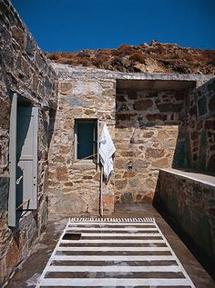 Let me take you to Serifos, one of the Cycladic islands where we'll enjoy the stunning Greek summer house of interior designer Paola Navone. Painted Rug, Painted Floors, Outdoor Stone, Outdoor Areas, Paola Navone, Outdoor Bathrooms, Outdoor Showers, Turbulence Deco, Greek House