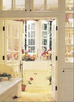 A view from the kitchen, with see-through cabinets,  looks through to the butler's pantry with its farm sink and casement windows that open to the garden.