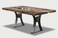 River run dining table Live Edge slabs of solid walnut have been inverted and inlaid with a glass 'tide pool' that runs the length of this stunning dining table. The steel base is finished in gun metal and features an inset river rock at each end, a perfect pairing.