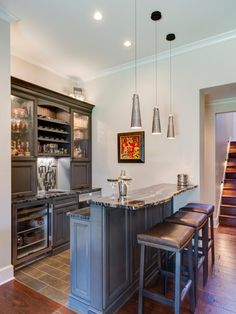 A wet bar downstairs boasts cool, contemporary lighting as well as sleek leather stools and a gorgeous marble countertop.