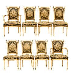 """Continental, likely French, early 20th century. A set of 8 Louis XVI style dining chairs, each polychromed in cream with gilt and green detailing, with applied finials, fluted stiles, decorative brass tacking, and round, tapering fluted legs, the seat and back upholstered in floral velvet. Apparently unmarked. Approximate height (of armchair) 38.5"""", width 22.75"""", seat depth 18.75"""", seat to floor 19"""", height (of side chair) 38.5"""", width 19.5"""", seat depth 16.5"""", seat to floor 19""""."""