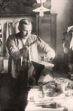 A war disabled man who lost both of his arms as a soldier in World War I works on a workbench using both of his arm prostheses. Date and place unknown. Photo: Berliner Verlag/Archiv