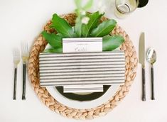 pretty wedding place setting with greenery and striped napkin over braided charger