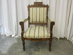 Late Victorian: Eastlake Gents Chair: walnut, simple curves, straight lines, rectangular carving in yoke, re-upholstered in striped fabric.