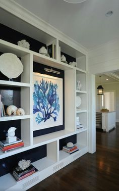 Bookshelf styling tip: display a collection. Here we have shells and coral around a coral print