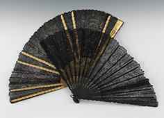 "Two Black Lace Hand Fans, ca. 1890    Both fans are apprx. 14-1/4""L, one with black painted wood sticks and the other gilt wood sticks, carved, impressed and pierced, with delicate black lace fans."