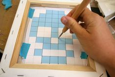 How to cross stitch on a canvas.  Use foam core when punching the holes so as not to stretch the canvas.  Clever!