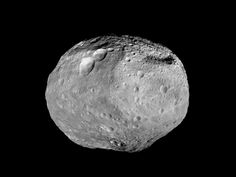 """Asteroid Vesta. The towering mountain at the south pole - more than twice the height of Mount Everest - is visible at the bottom of the image. The set of three craters known as the """"snowman"""" can be seen at the top left. (Image: Dawn mission)"""