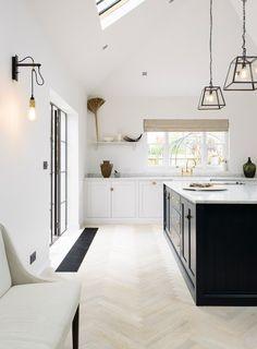 light wood floors, black island, white cabinets