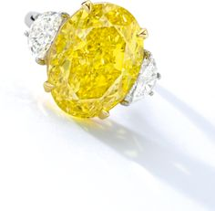 ALT VIEW. Important Fancy Vivid Yellow Diamond and Diamond Ring. Set with an oval fancy vivid yellow diamond weighing 11.46 carats, flanked by two half-moon-shaped diamonds weighing approximately 1.40 carats in total, mounted in platinum and 18 karat yellow gold. Ring size: 6