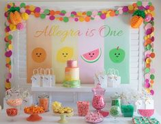 Tutti Frutti Themed First Birthday - The backdrop is the sweetest and the paper dot garland and pineapple honeycomb's add extra charm. More details to L♥VE are the fruit cake pops, amazing cake, fruity props and adorable printable's on the chocolates and drinks.